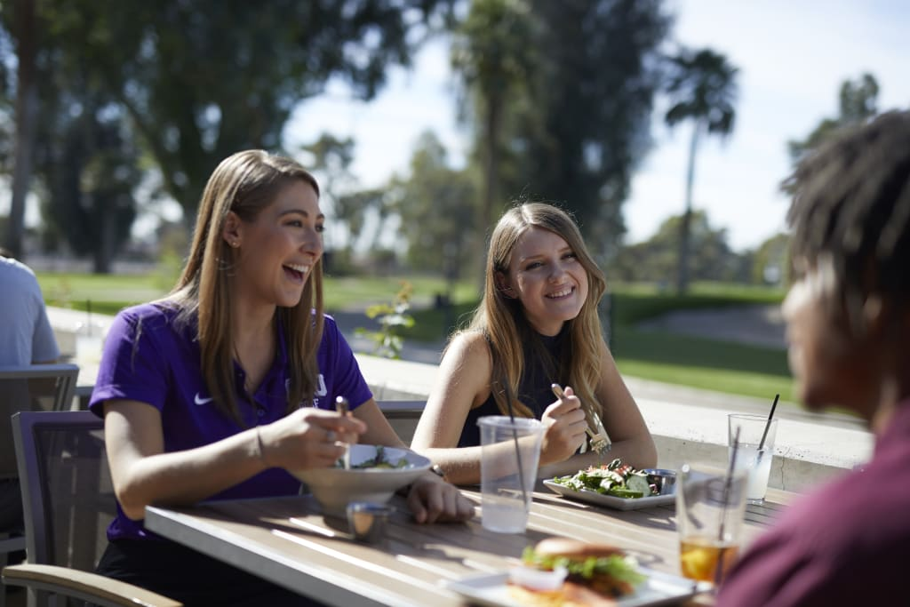Two women enjoying food at GCU Golf Course Restaurant Lope House