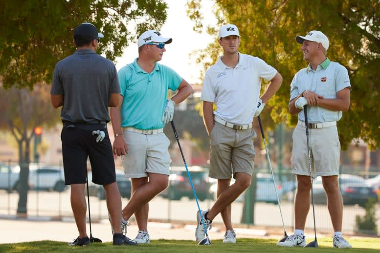 Four golfers standing and talking