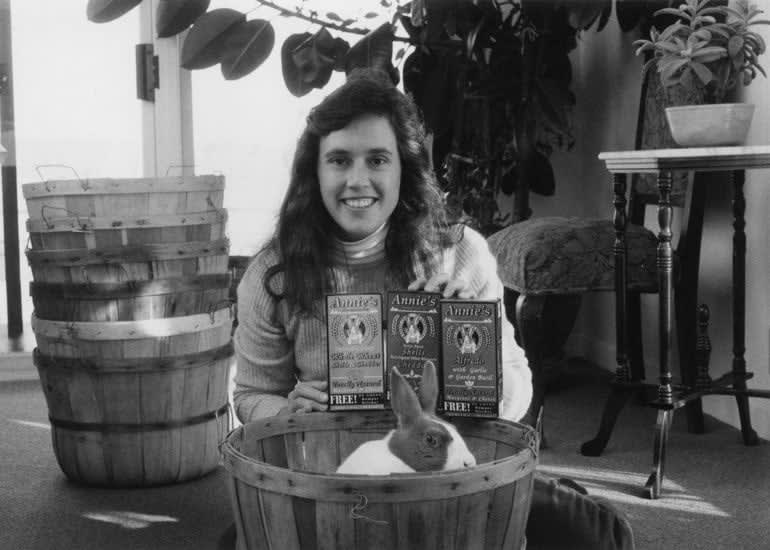 Annie Withey holding 3 boxes of Annie's Mac and Cheese. Her pet rabbit sits in a basket in front of her.