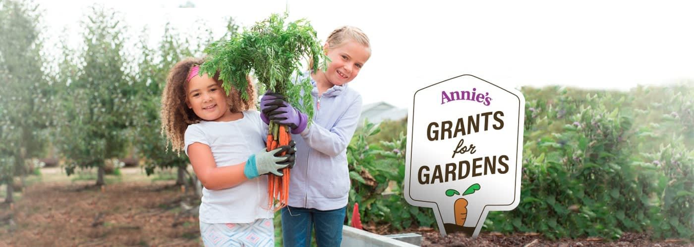 "Two smiling children, holding up a big bunch of carrots, standing next to a sign that reads ""Annie's Grants for Gardens"""