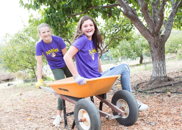 Two pre-teen girls laughing, while one pushes the other in a wheelbarrow