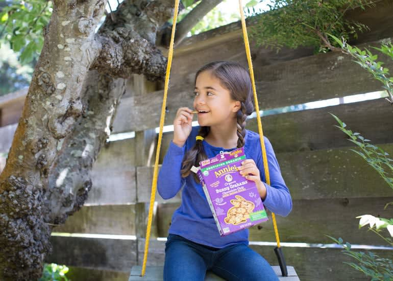 A young girl with braided hair sitting in a swing, eating Annie's Bunny Grahams from the box