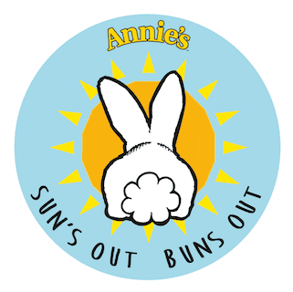"""A circular aqua colored sticker showing the backside of a rabbit in front of the sun. It says """"Annie's - Sun's out Buns out"""""""