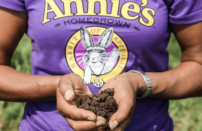 Women holding organic soil with earthworm in it