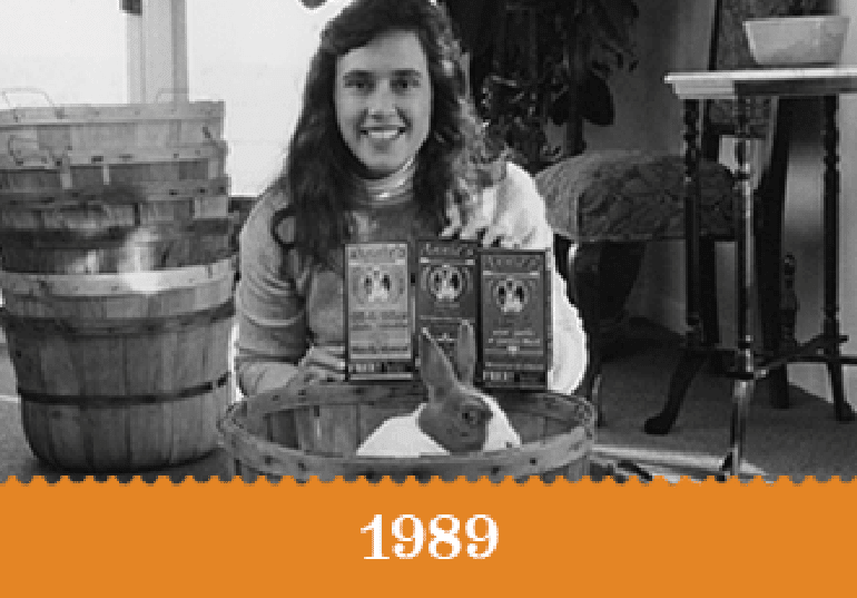 Year 1989 - A black and white photo of Annie with Bernie and 3 boxes of Mac and Cheese