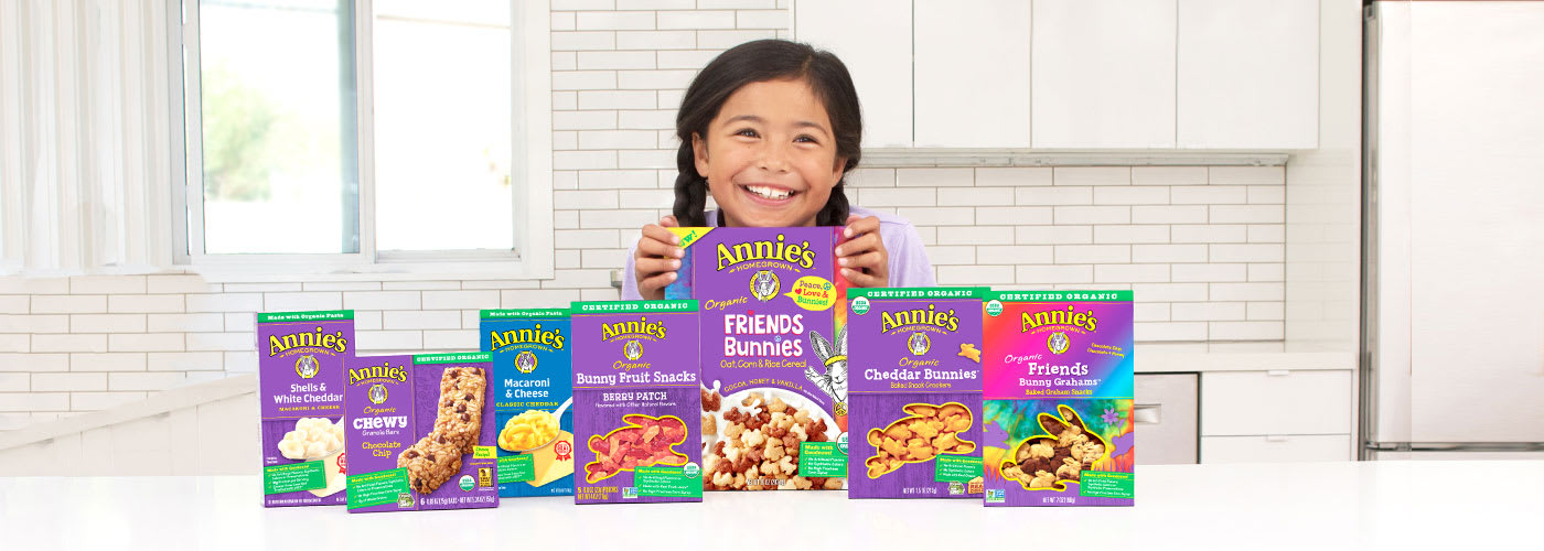 A smiling little girl sitting at a counter surrounded by boxes of Annie's crackers, cereals, and snack bars.