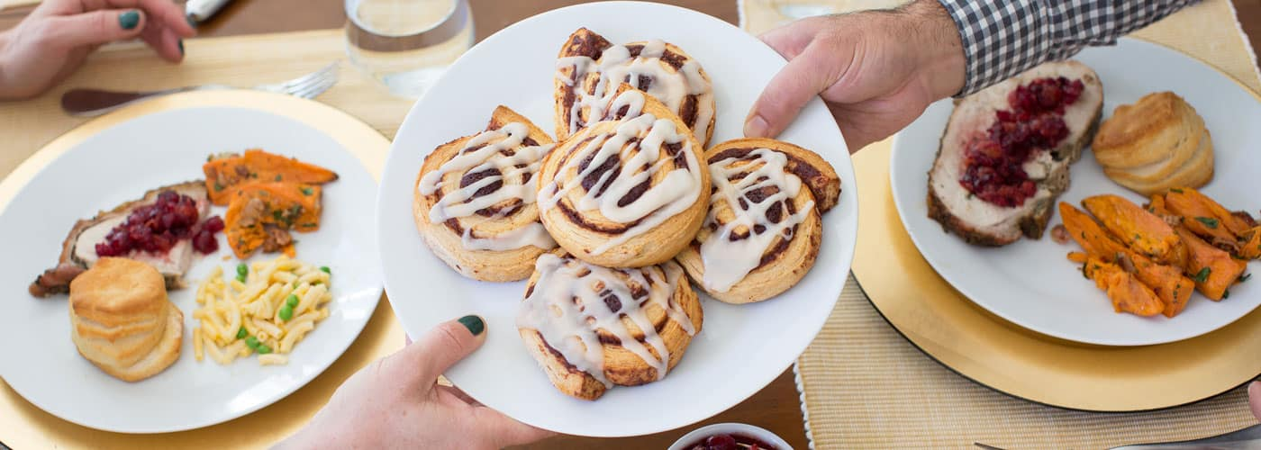 Hands passing a plate of cinnamon rolls across a dinner table