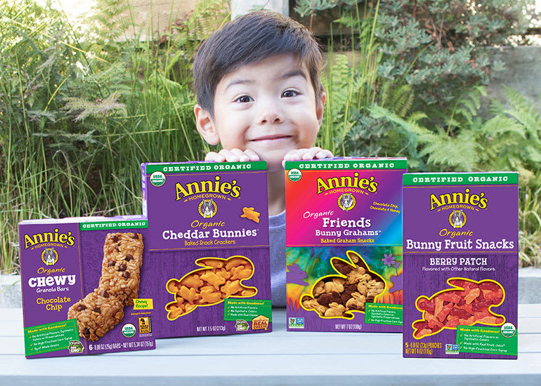 A smiling little boy peeking out from behind boxes of Annie's fruit snacks, cheddar bunnies, and granola bars