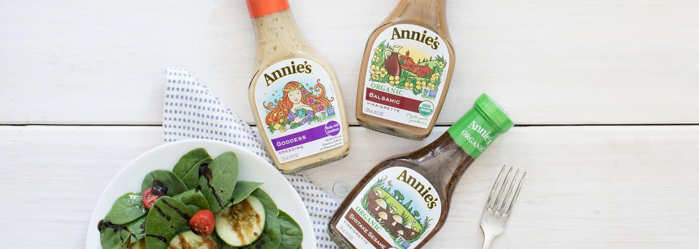 A green salad sitting next to bottles of Annie's Goddess, Organic Balsamic, and Organic Shiitake Sesame dressings