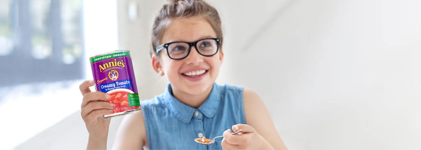 A smiling girl wearing glasses holds up a spoon and a can of Annie's creamy tomato and bunny pasta soup.