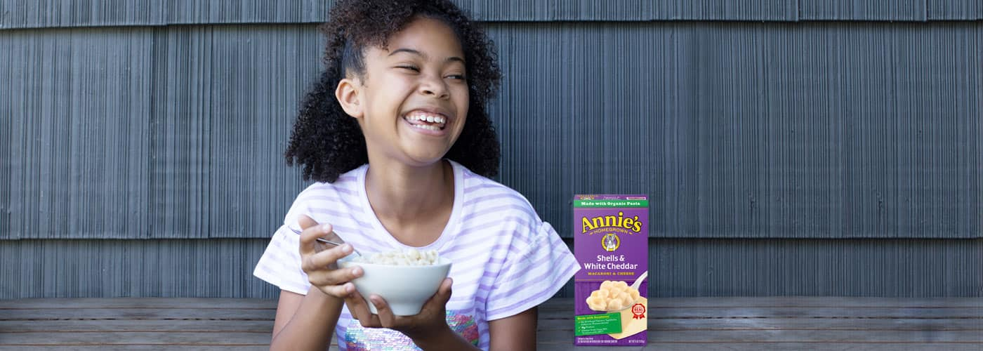 A giggling girl eating Annie's Shells and White Cheddar from a bowl