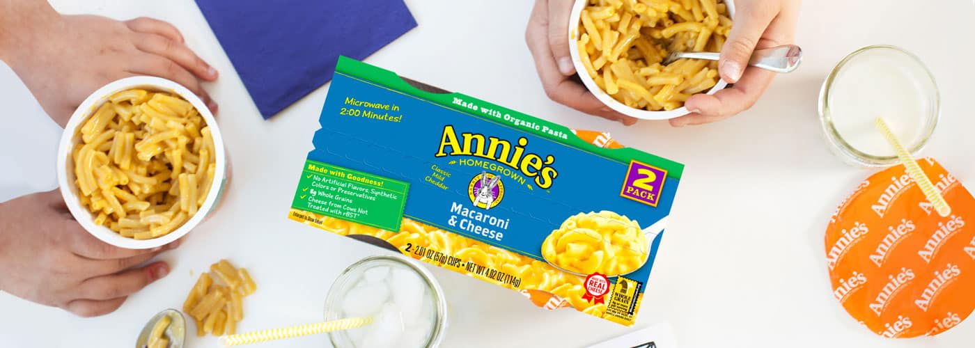 A box of Annie's microwave macaroni and cheese on a table with people eating from microwavable cups