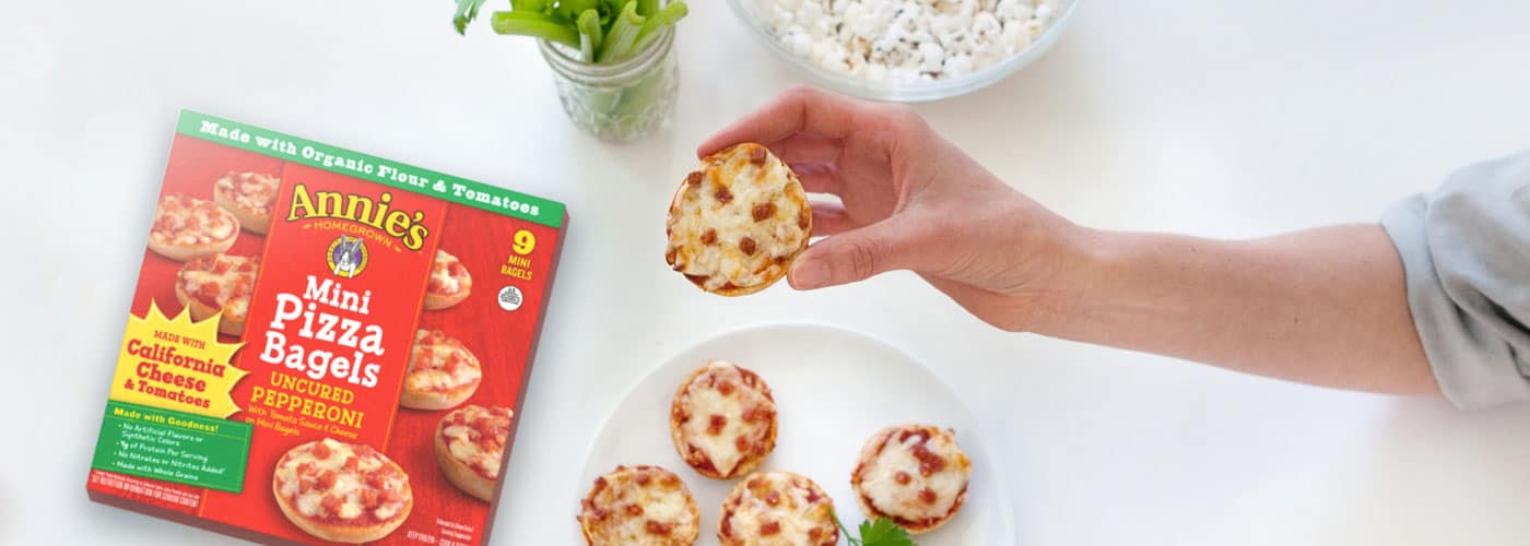 A hand picks up a mini pizza bagel with uncured pepperoni from a plate. The red box sits next to the plate.