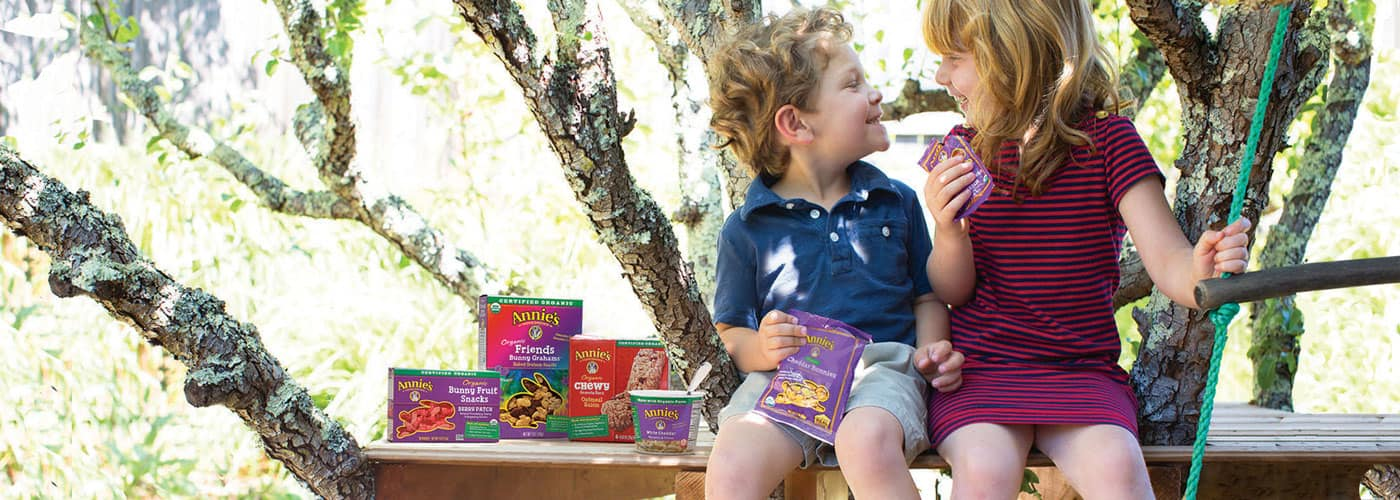 A boy and a girl smiling at each other while sitting on a wooden bench. A pile of Annie's fruit snack and granola bar boxes sit beside them.