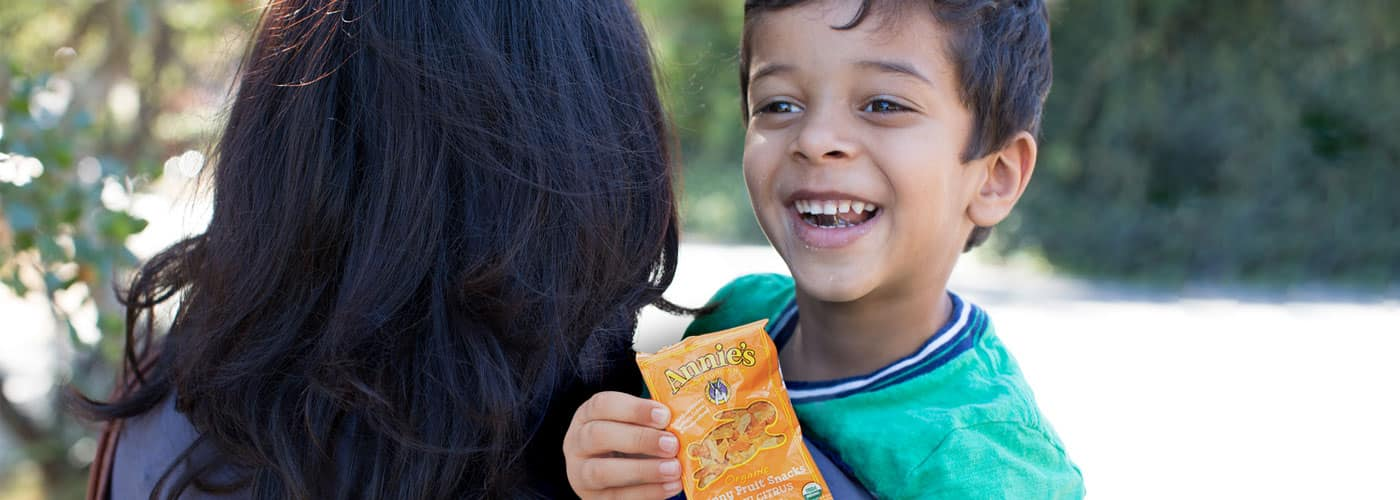 A laughing boy being carried by a woman while eating a packet of Annie's vegan fruit snacks.