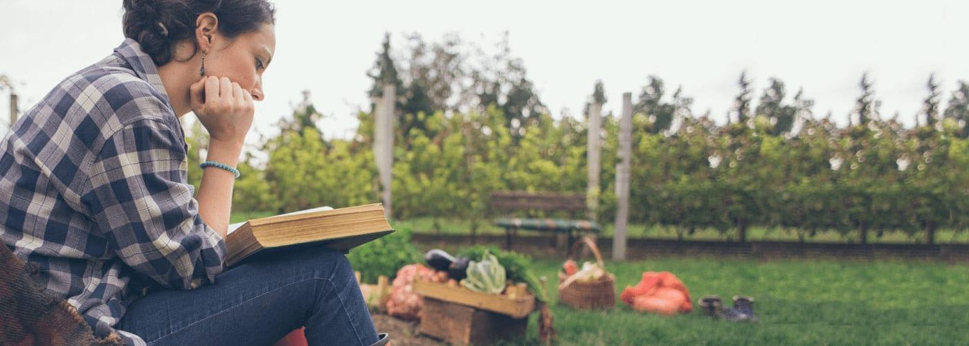a girl reading a book in a garden
