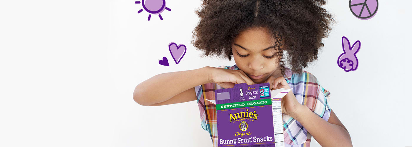 Little girl reaching into box of Annie's Fruit Snacks