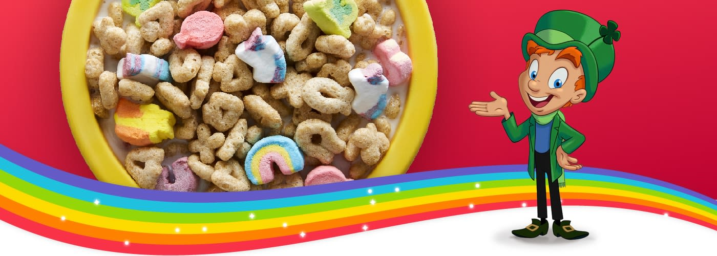 Lucky the Leprechaun standing next to a bowl of Lucky Charms on a rainbow