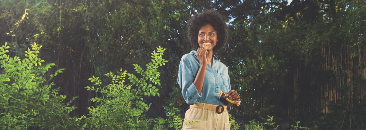 A brown with curly black hair eating Fruit and nut bars standing in front of forest