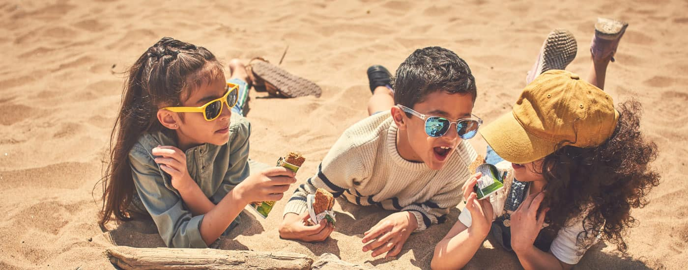 Three children lay in the sand eating Nature Valley bars and wearing sunglasses.