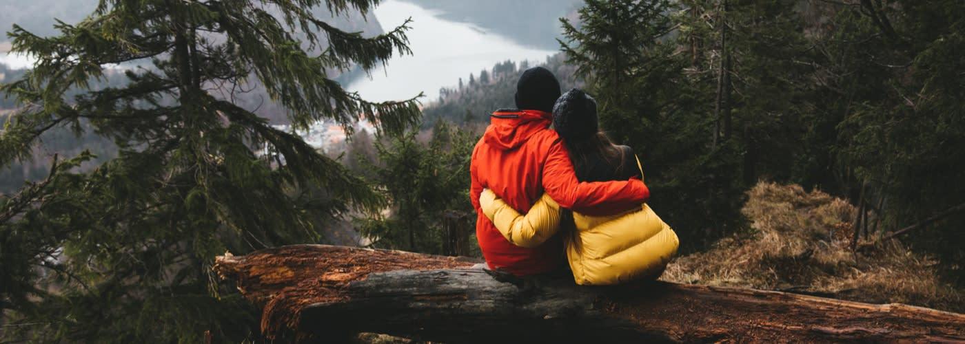 Couple sat on broken trunk of tree in forest enjoying landscape view