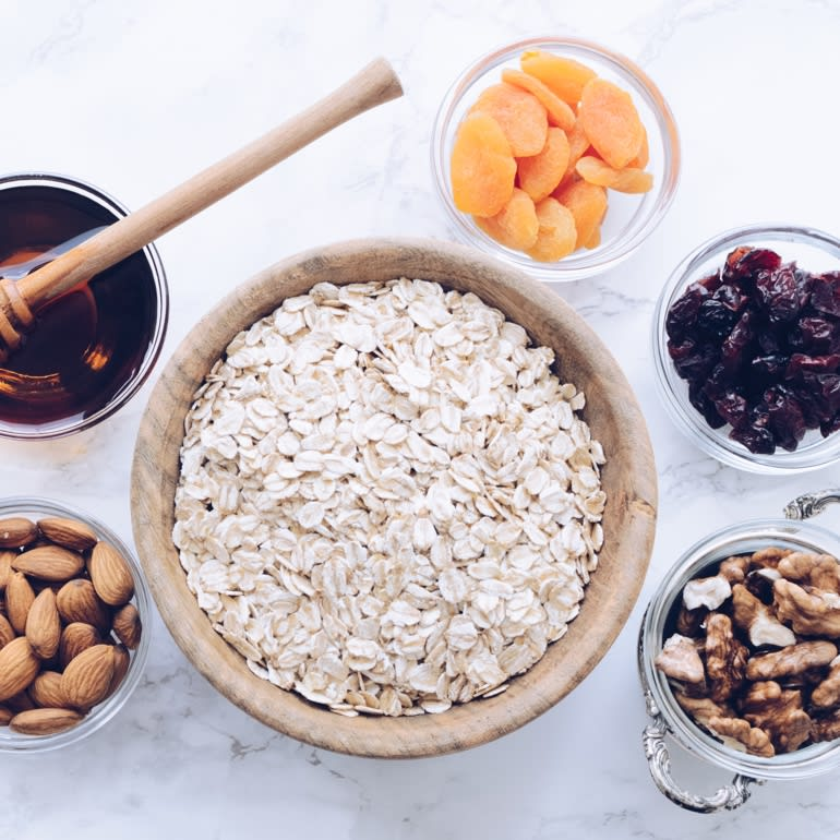 A dozen small glass bowls sitting on a marble countertop. The bowls contain ingredients such as raw almonds, pepitas, oats, walnuts, dried cranberries, coconut shavings, and dried apricots.