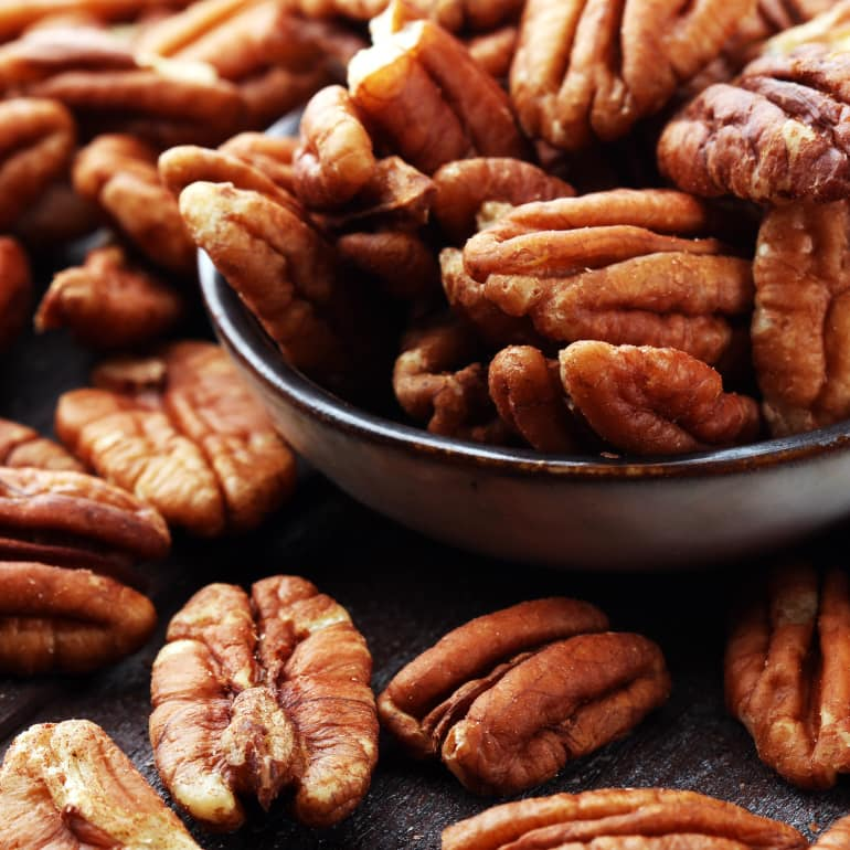 Whole pecans overflowing from a bowl.