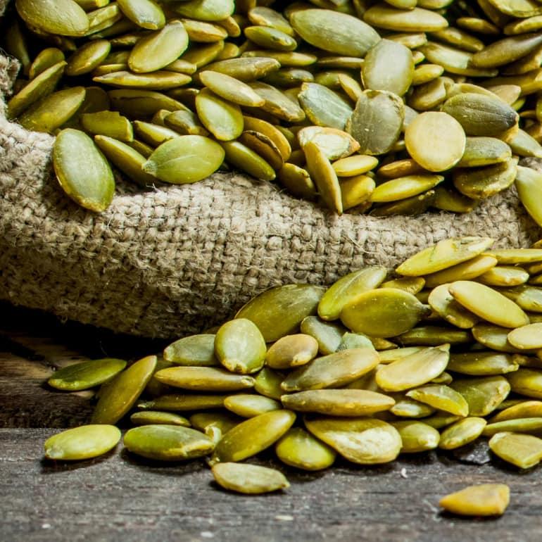 A burlap sack of green pumpkin seeds.