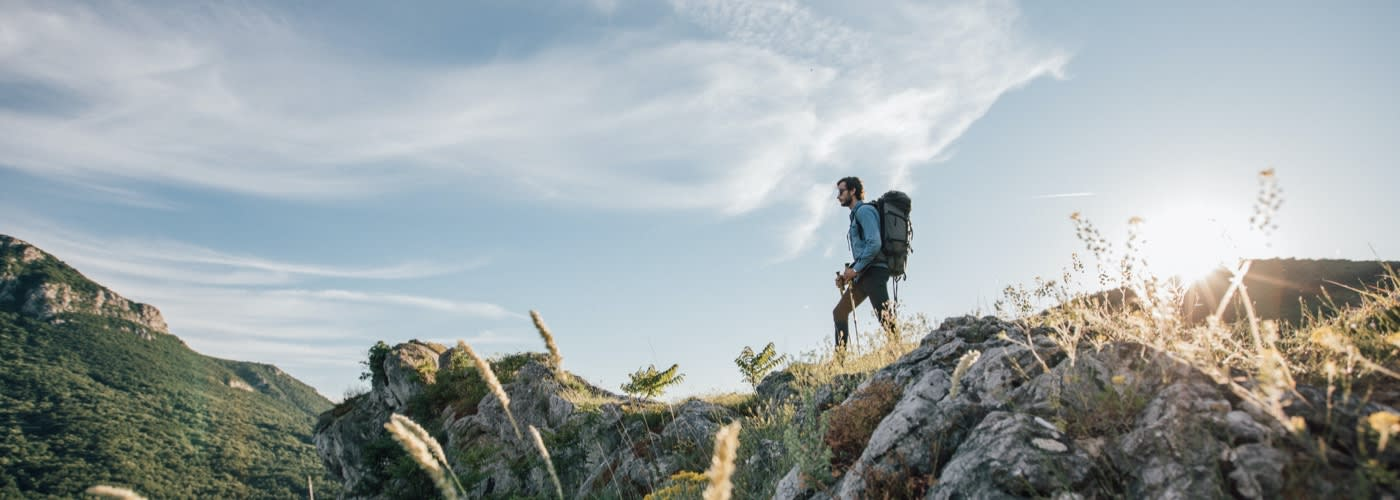 A man wearing hiking backpack standing in sunrise spring rays peaking through forest