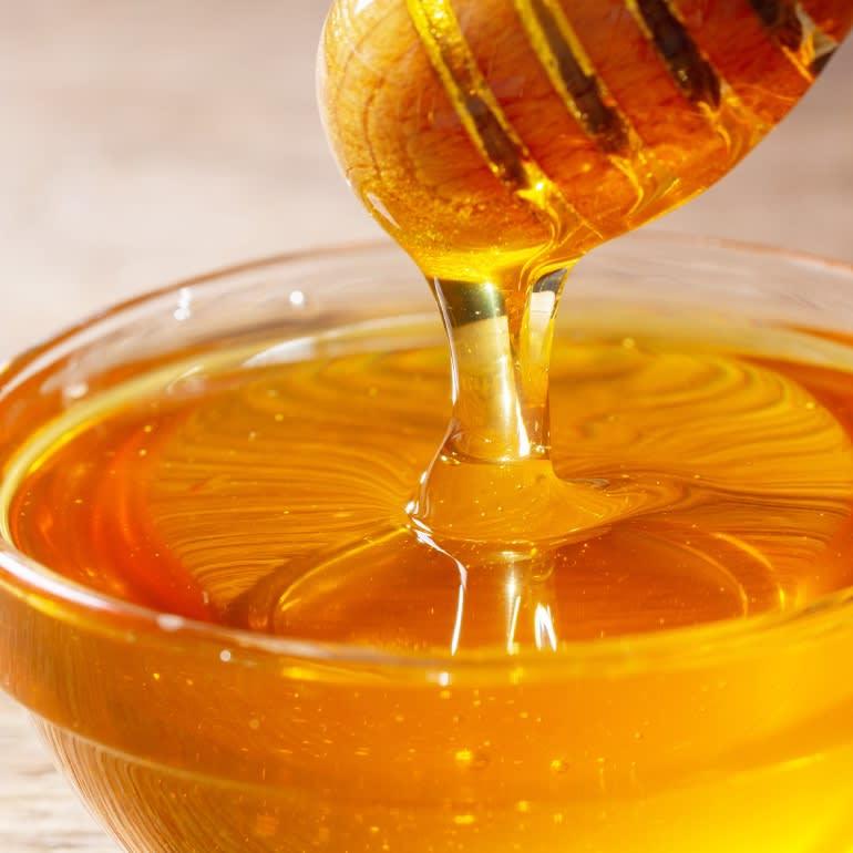 A honey wand dripping golden honey into a glass bowl.