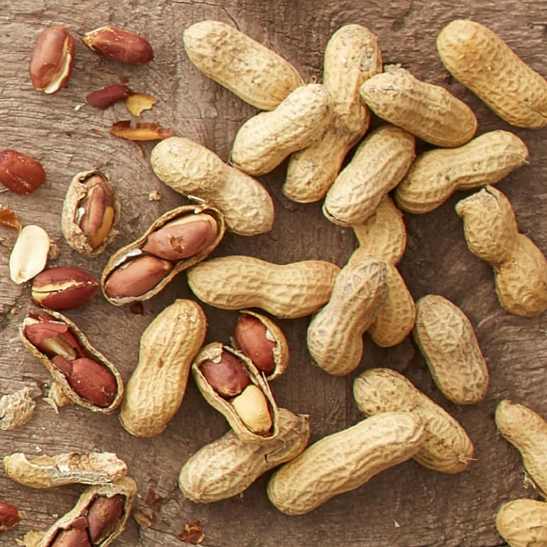 Whole peanuts in their shells are scattered on a table. Some have cracked open to reveal the peanuts inside.