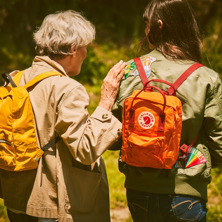 An elderly woman walks with her hand on the shoulder of a young girl wearing a backpack.