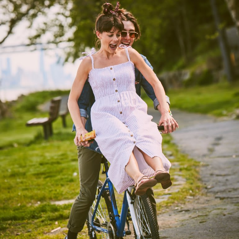 A woman in a white sundress rides on the handlebars of a man riding a bike.