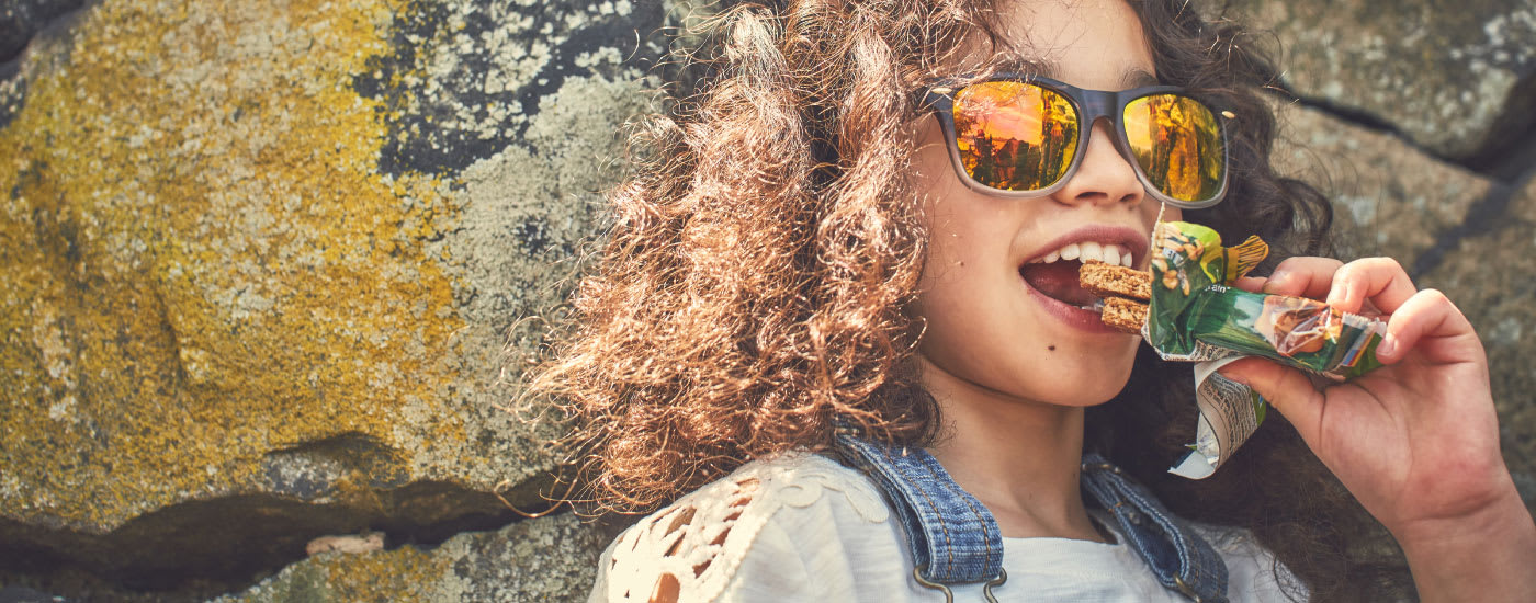 A curly haired girl wearing sunglasses, leaning against a rock wall and eating a Nature Valley Crunchy bar.