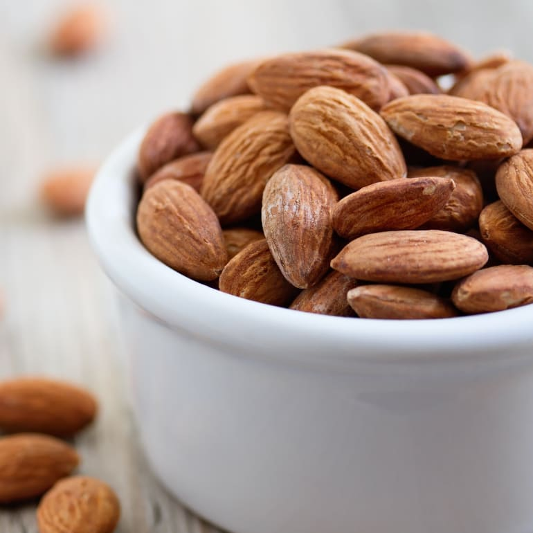 A white ramekin filled with whole almonds.