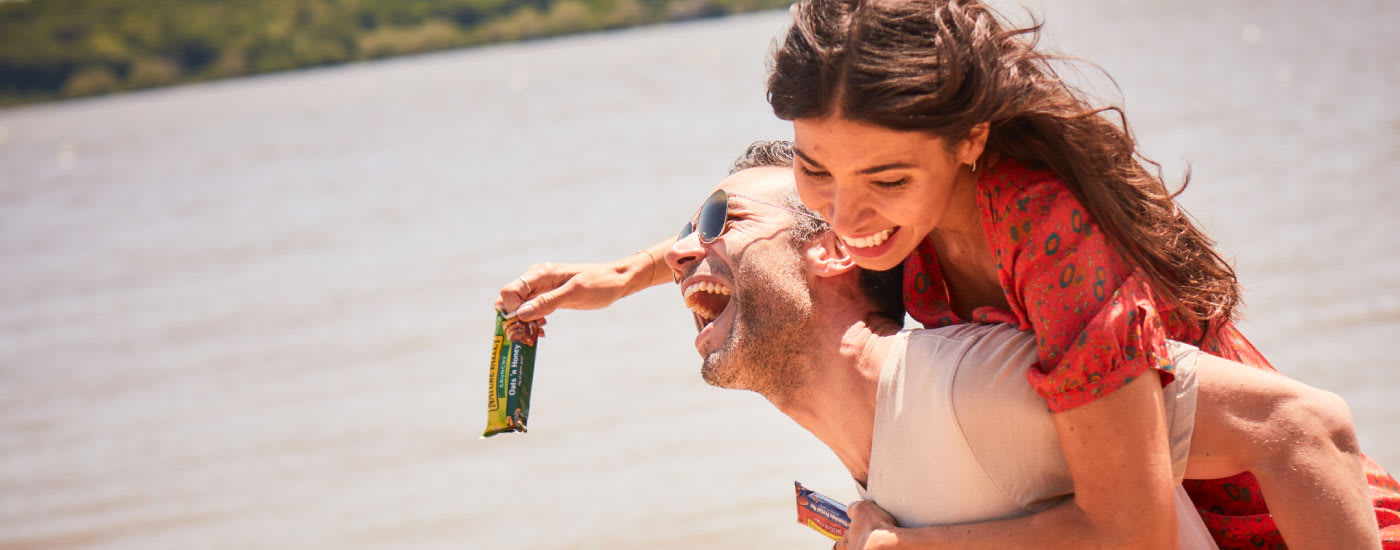 A woman holding a Nature Valley bar rides on a laughing man's back.