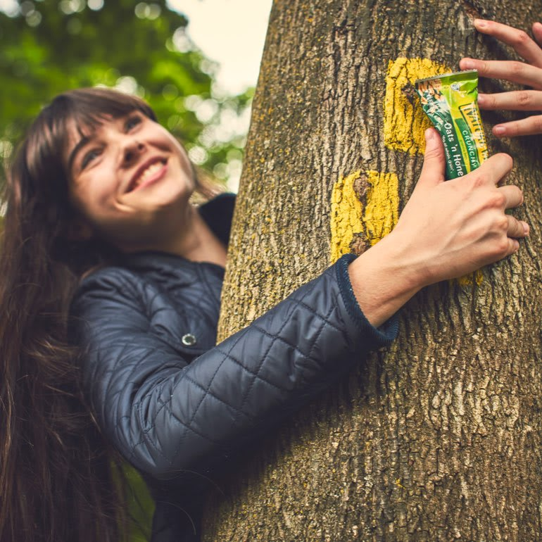 A smiling dark-haired woman hugs a tree while holding a Nature Valley bar.