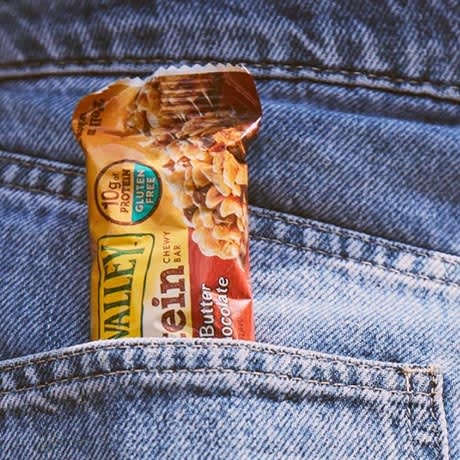 A Gluten-free Nature Valley granola bar sticking out of a pocket in a pair of denim jeans.