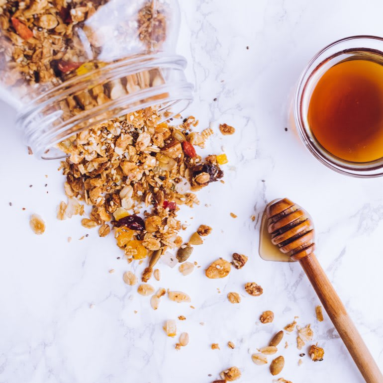 Granola spills out of a glass jar onto a marble countertop. A bowl of honey sits nearby.