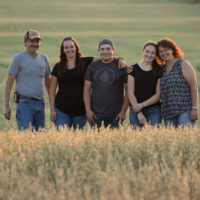 A group of people standing in Oats farm