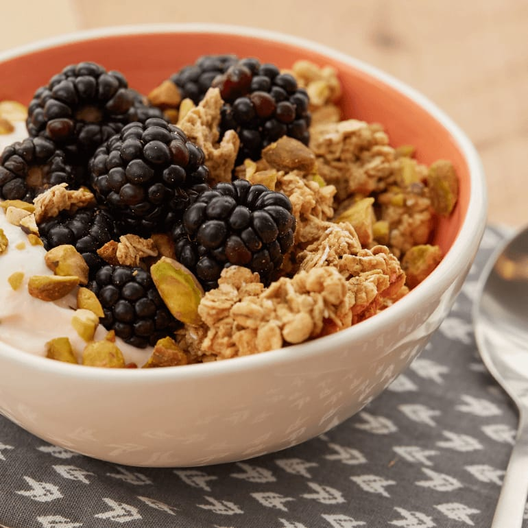 bowl full of peachy berry along with granola yogurt