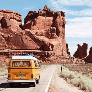 A yellow van on road surrounded by brown unstructured mountains - Link to social post