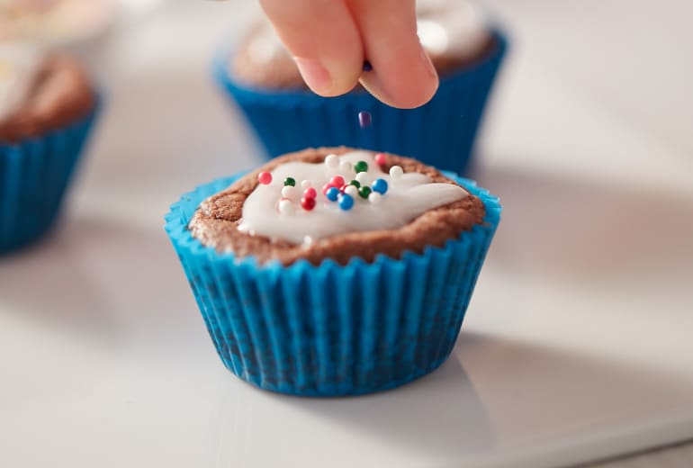Close up on someone's hand sprinkling a brownie bite with sprinkles