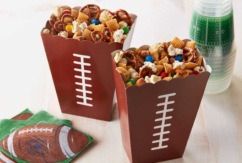 two cups of chex tailgate party mix in football shaped cones