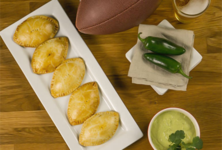 football empanadas on a white serving platter