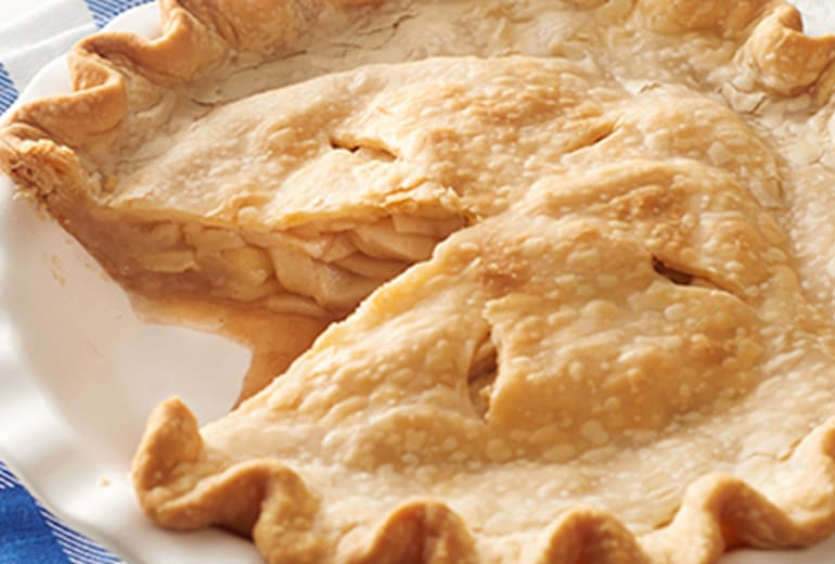 close up of a perfect apple pie with one slice missing