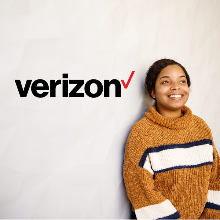 Young African American woman smiling while leaning against a wall with Verizon logo