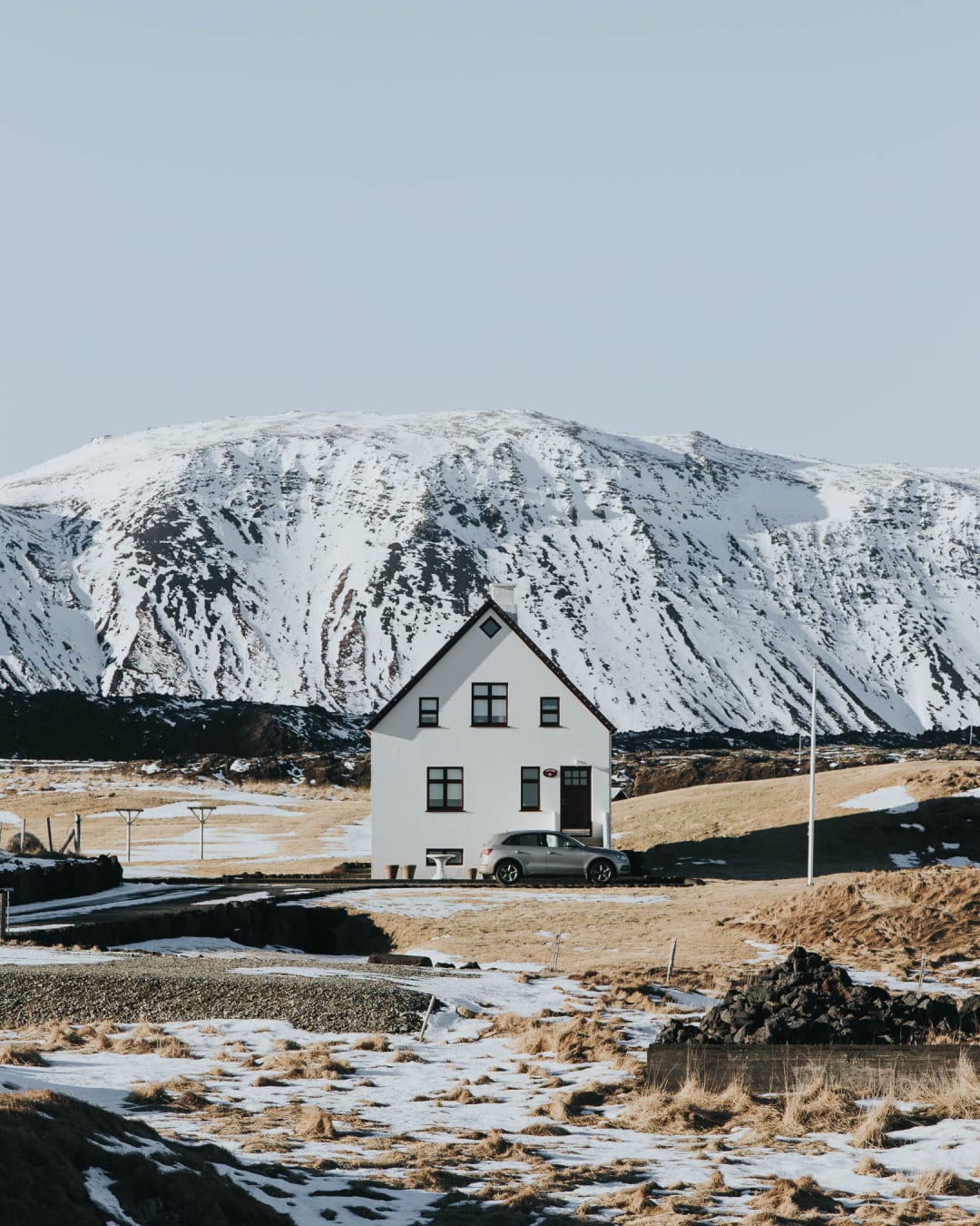 minimal house and car in front of snowy mountain landscape photography of Iceland