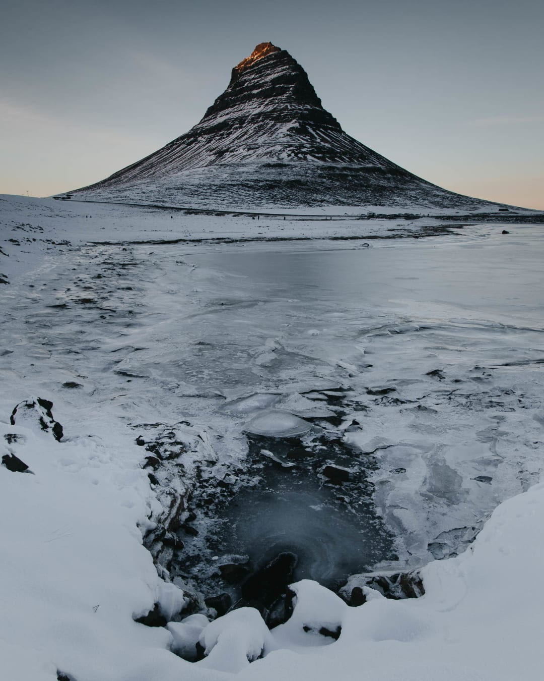 ice and snow at the foot of Kirkjufell mountain at sunset landscape photography of Iceland