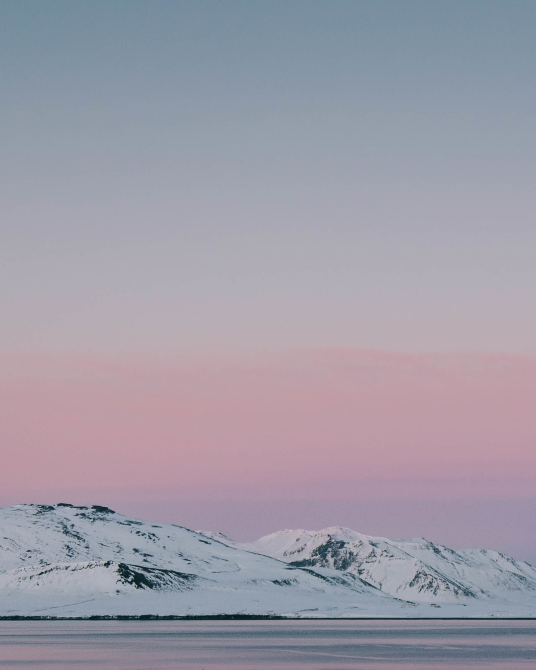 pink and red hue sky at sunset near a snowy Kirkjufell landscape photography of Iceland